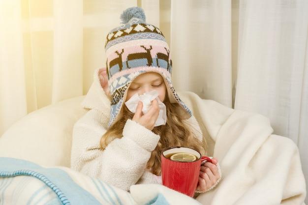 Garoto garota espirra em um lenço em casa
