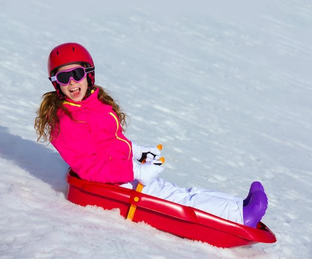 Garoto garota jogando trenó na neve do inverno