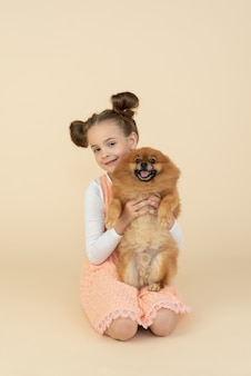 Garoto garota sentada e segurando o cão spitz