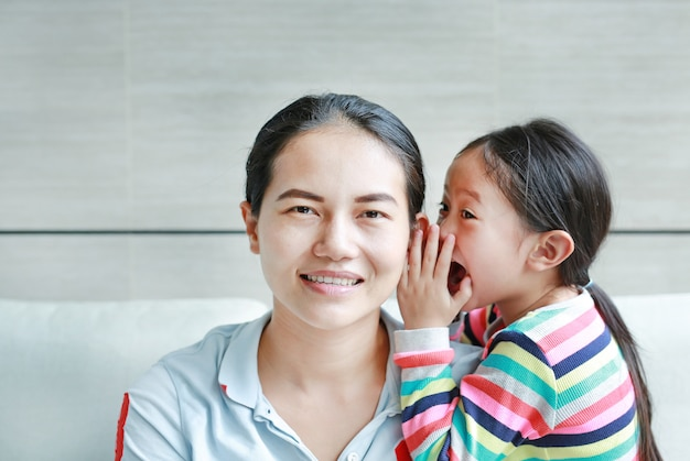 Garoto garota sussurrando fofoca um algo para o ouvido da mãe.