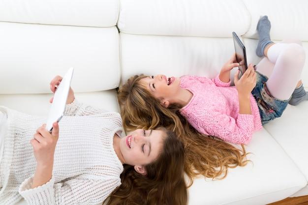 Garoto garotas se divertindo brincando com o tablet pc deitado sofá