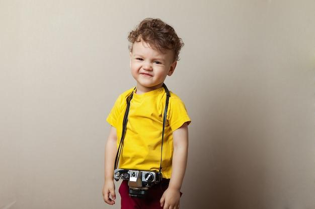 Garoto garoto 2 anos de idade vestindo roupas amarelas segurar a câmera