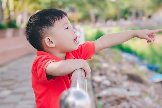 Garoto garoto apontando com o dedo para o rio, em um estado de espírito chocante.
