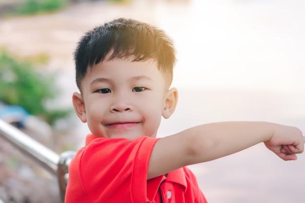 Garoto garoto apontando com o dedo para o rio, em um rosto sorridente.