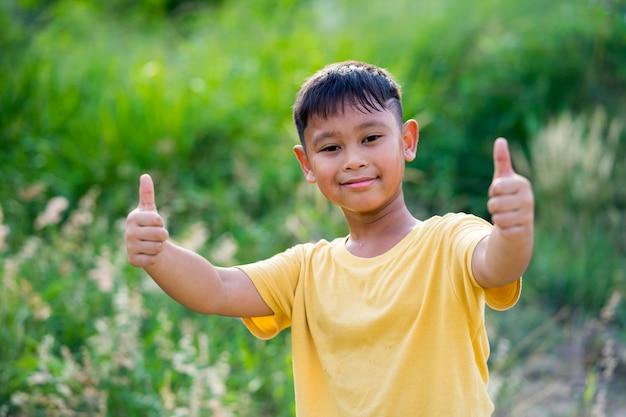 Garoto garoto asiático brincando na natureza está segurando um polegar para