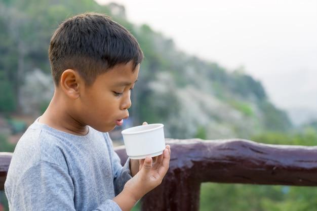 Garoto garoto asiático é beber água do copo. com vista para a montanha de fundo