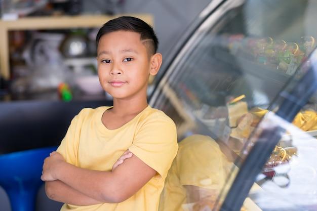 Garoto garoto asiático esperando na loja de padaria e escolhendo a padaria que ele gosta