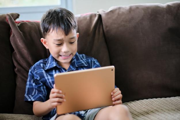 Garoto garoto asiático jogando no tablet inteligente torcendo ação