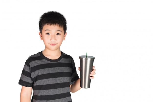 Garoto garoto asiático, segurando o copo de aço inoxidável com palha