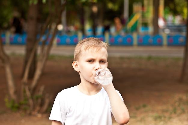 Garoto garoto bebendo água de uma garrafa ao ar livre em um parque