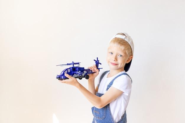 Garoto garoto de jeans azul brincando com um helicóptero de brinquedo