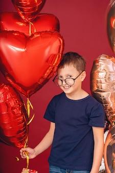 Garoto garoto engraçado em copos, coração de cor diferente, balões estrela para dia dos namorados