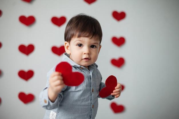 Garoto garoto feliz em uma camisa com uma gravata borboleta vermelha oferece um cartão de dia dos namorados contra uma parede cinza com corações no dia dos namorados.