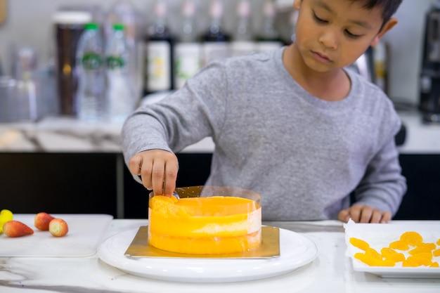 Garoto garoto feliz fazendo um bolo