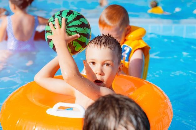 Garoto garoto jogando piscina ao ar livre do resort. em um círculo amarelo inflável com uma bola. as crianças brincam com brinquedos aquáticos. espirrando ao redor. esfrie o calor. Foto Premium
