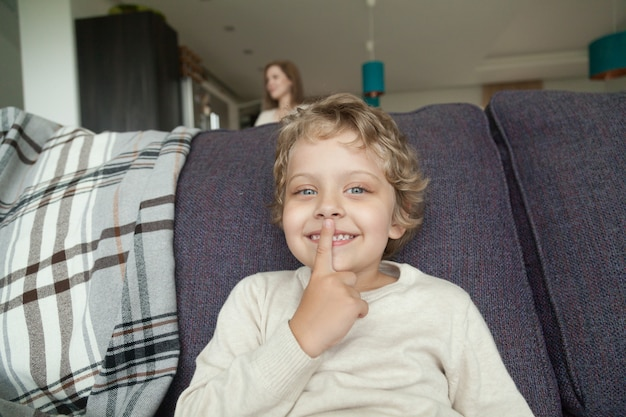 Garoto garoto segurando o dedo nos lábios brincando de esconde-esconde