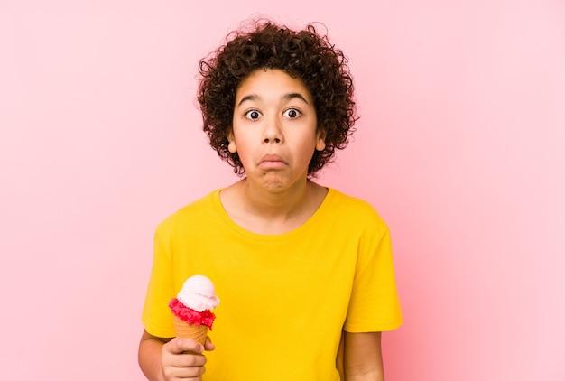 Garoto garoto segurando um sorvete isolado encolhe os ombros e abre os olhos confusos.