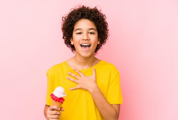 Garoto garoto segurando um sorvete isolado ri alto, mantendo a mão no peito.