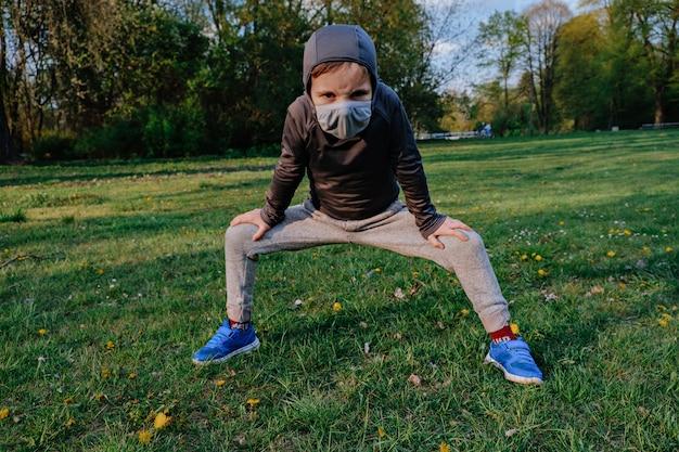 Garoto garoto vestindo como ninja faz exercícios diferentes ao ar livre