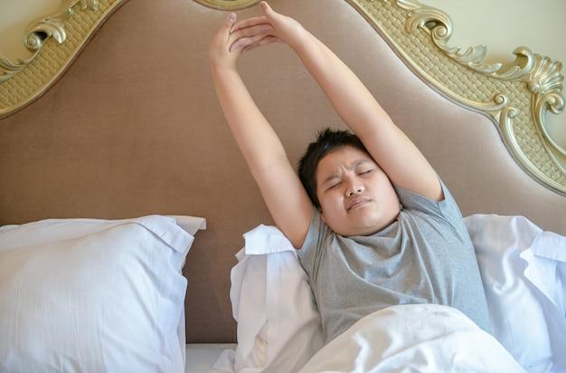 Garoto gordo asiático acorda e se espreguiçando na cama pela manhã, conceito saudável
