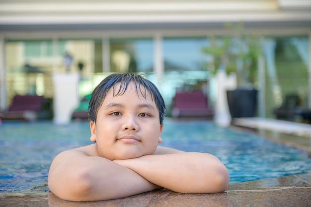 Garoto gordo feliz na piscina, relaxe e faça exercícios.