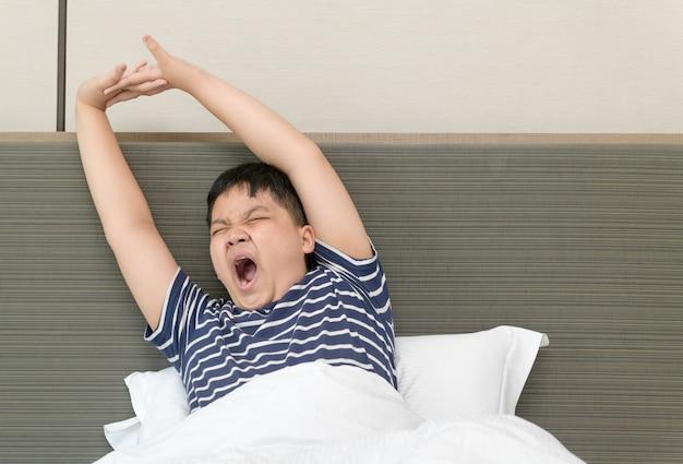 Garoto gordo obeso acorda e se espreguiçando na cama de manhã. conceito de mundo de saúde e bom dia