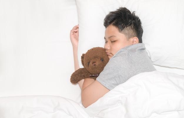 Garoto gordo obeso está dormindo com um ursinho de pelúcia em sua cama em casa, doce sonho e conceito de descanso