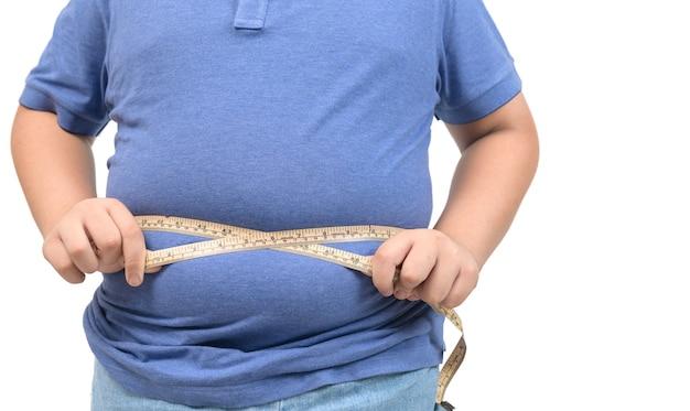 Garoto gordo obeso medindo fita de estômago isolada no fundo branco, conceito saudável e de perder peso
