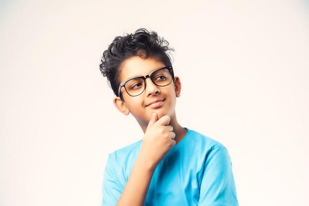 Garoto indiano do sexo masculino pensando contra uma parede branca, garotinho asiático usa óculos e encontra solução para algo