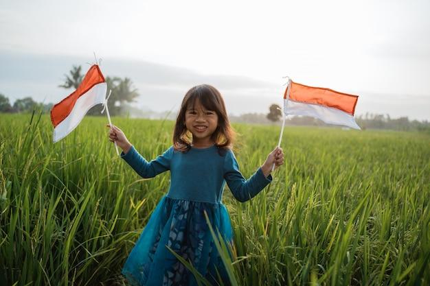 Garoto indonésio com bandeira nacional