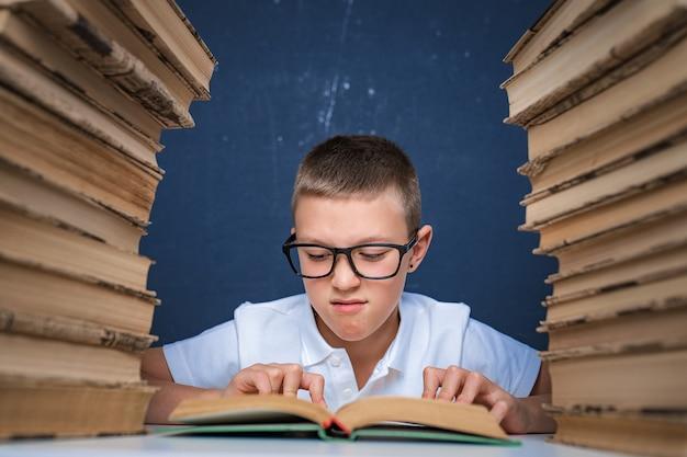 Garoto inteligente de óculos sentado entre duas pilhas de livros e lendo o livro pensativamente