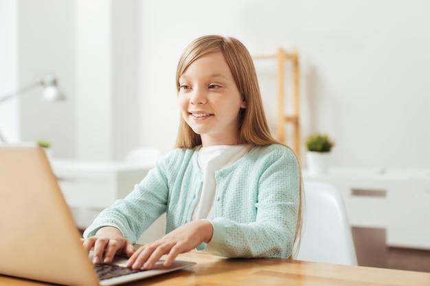Garoto inteligente. garota admirável e produtiva usando o computador enquanto está sentada à mesa