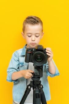 Garoto intrigado bonito ajusta a câmera no tripé