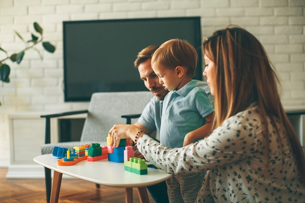 Garoto jogando brinquedos com a mãe e o pai em casa