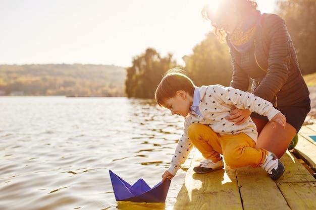 Garoto jogando com navio de papel de brinquedo à beira do lago