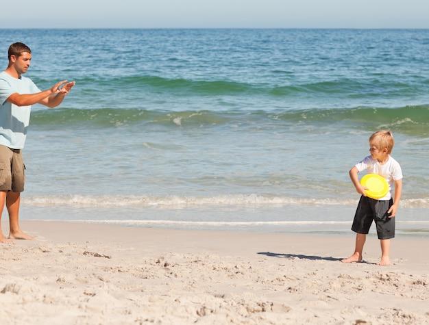 Garoto jogando frisbee com seu pai