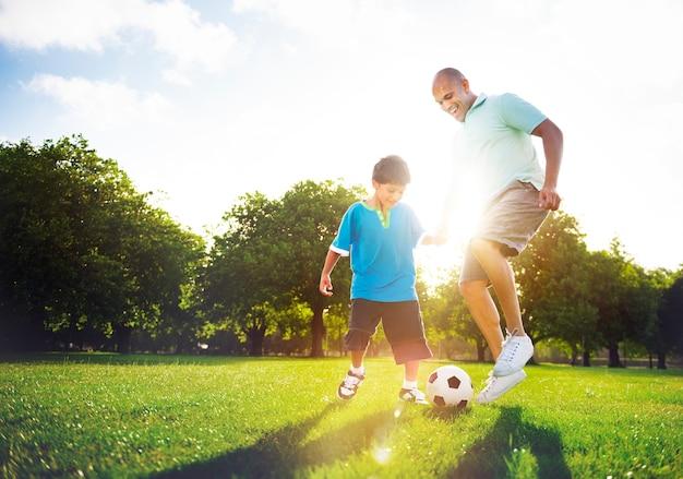Garoto jogando futebol com seu pai.