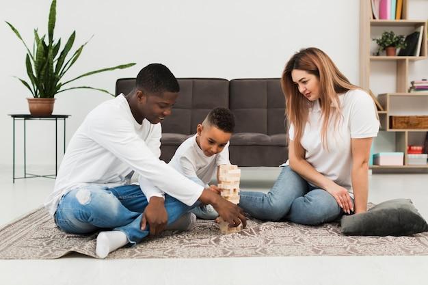 Garoto jogando jogo de torre de madeira com seus pais