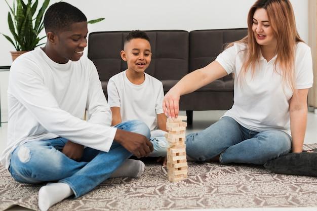 Garoto jogando um jogo com os pais em casa