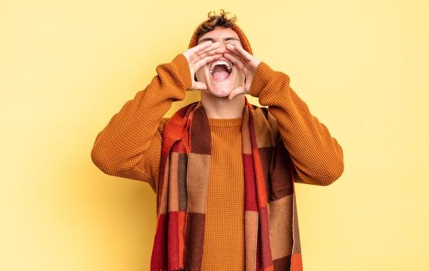 Garoto jovem adolescente se sentindo feliz, animado e positivo, dando um grande grito com as mãos perto da boca, gritando
