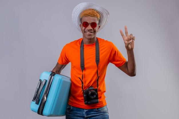 Garoto jovem afro-americano bonito com chapéu de verão vestindo camiseta laranja segurando uma mala de viagem, olhando para a câmera, sorrindo amigável mostrando o número dois ou o sinal da vitória sobre branco backgrou