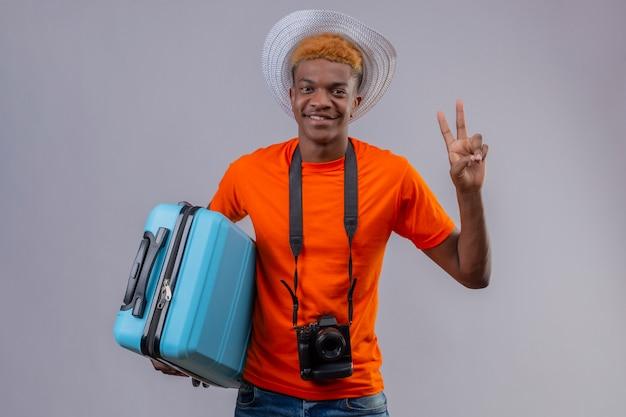 Garoto jovem afro-americano bonito com chapéu de verão, vestindo uma camiseta laranja, segurando uma mala de viagem, olhando para a câmera, sorrindo amigável, mostrando o número dois ou o sinal da vitória sobre fundo branco