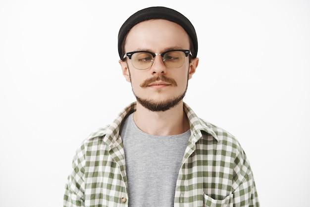 Garoto jovem bonito e brincalhão com bigode e barba de óculos e gorro preto da moda olhando para a ponta do nariz, apertando os olhos e fazendo caretas enquanto brinca sem ter nada para fazer e entediado
