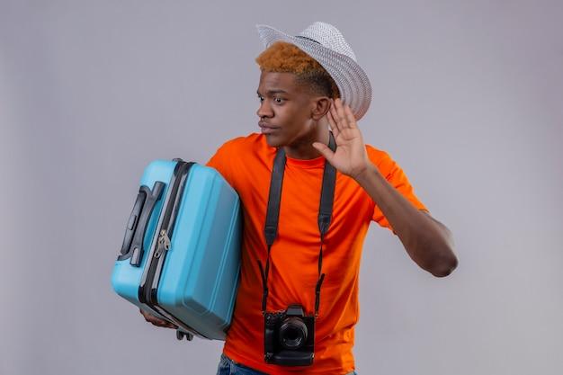 Garoto jovem bonito viajante afro-americano com chapéu de verão, vestindo uma camiseta laranja, segurando uma mala de viagem, segurando a mão perto de sua orelha, tentando ouvir a conversa de alguém no fundo branco
