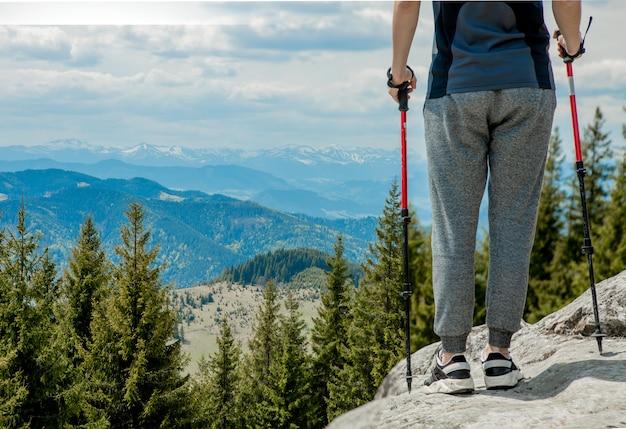 Garoto jovem, despreocupado, subindo enormes pedras sólidas, usando bastões para facilitar o acesso ao topo, apreciando a vista de maravilhas naturais no caminho