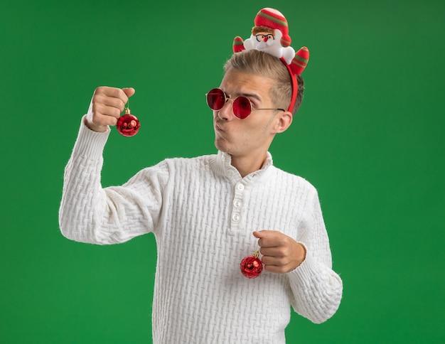 Garoto jovem duvidoso com bandana de papai noel e óculos segurando enfeites de natal, olhando para um deles isolado no fundo verde