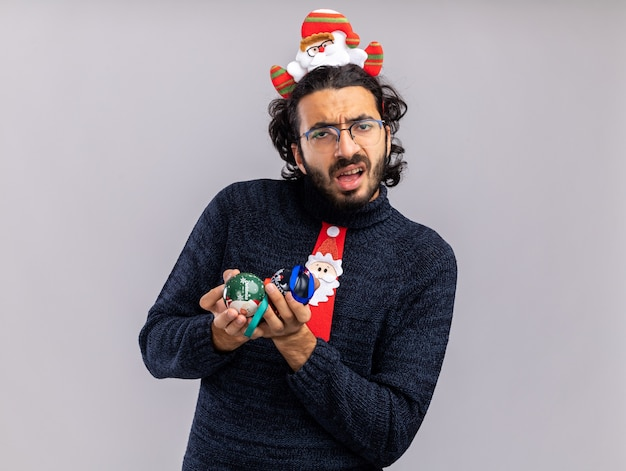 Garoto jovem e bonito confuso usando gravata de natal com argola de cabelo segurando bolas de natal isoladas no fundo branco