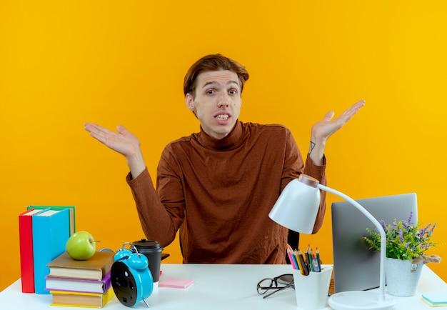Garoto jovem e confuso, sentado à mesa com as ferramentas da escola, abre as mãos