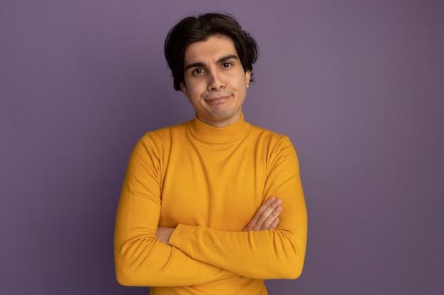Garoto jovem e desagradável vestindo uma blusa de gola alta amarela cruzando as mãos isoladas na parede roxa