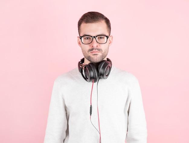Garoto jovem e fofo sério ouvindo música em grandes fones de ouvido brancos na parede rosa, em um moletom branco, dia mundial do dj